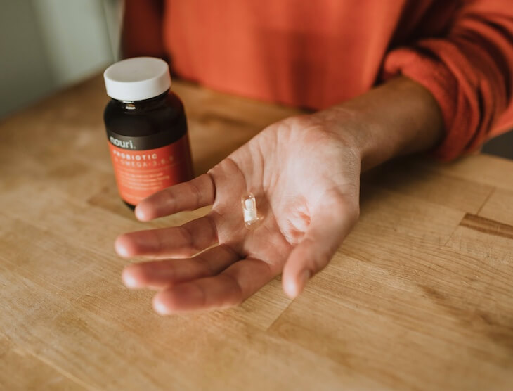 probiotic-bottle-on-the-table-and-a-capsule-on-hand